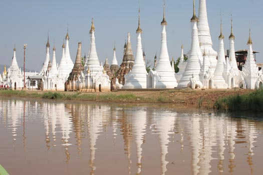White stupas reflected in the muddy waters of Inle Lake